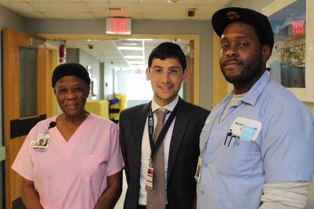 two males and female employees smile for camera