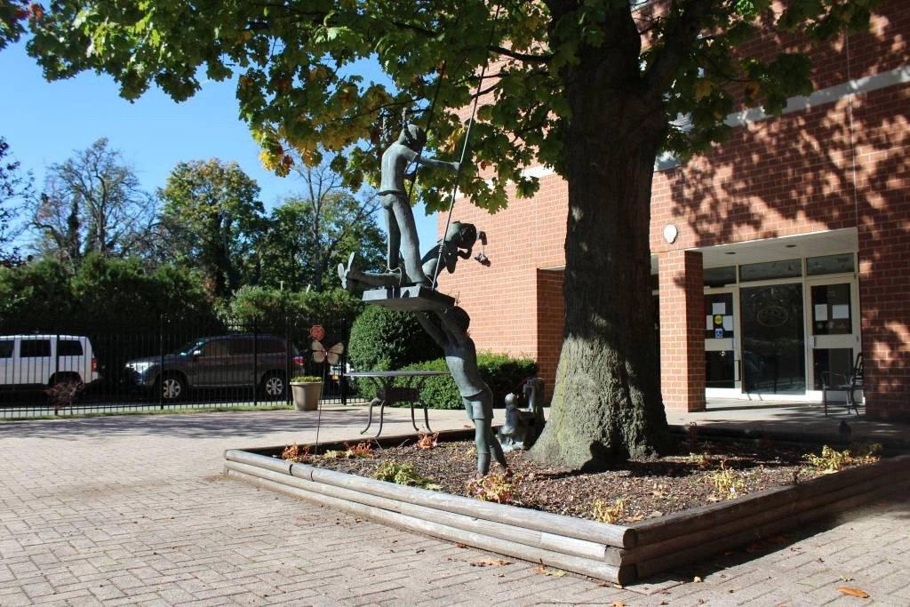 statue next to tree outside of Nassau Rehabilitation & Nursing Center