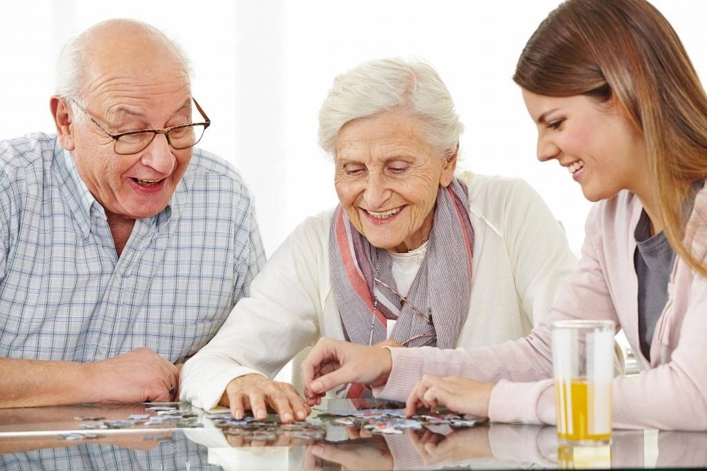 Nurse doing a puzzle with elderly couple