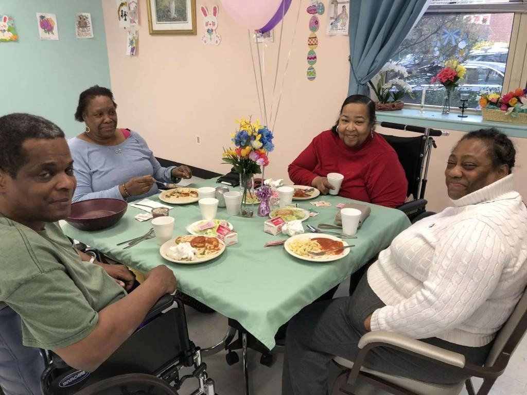 Residents sitting at table, smiling for camera