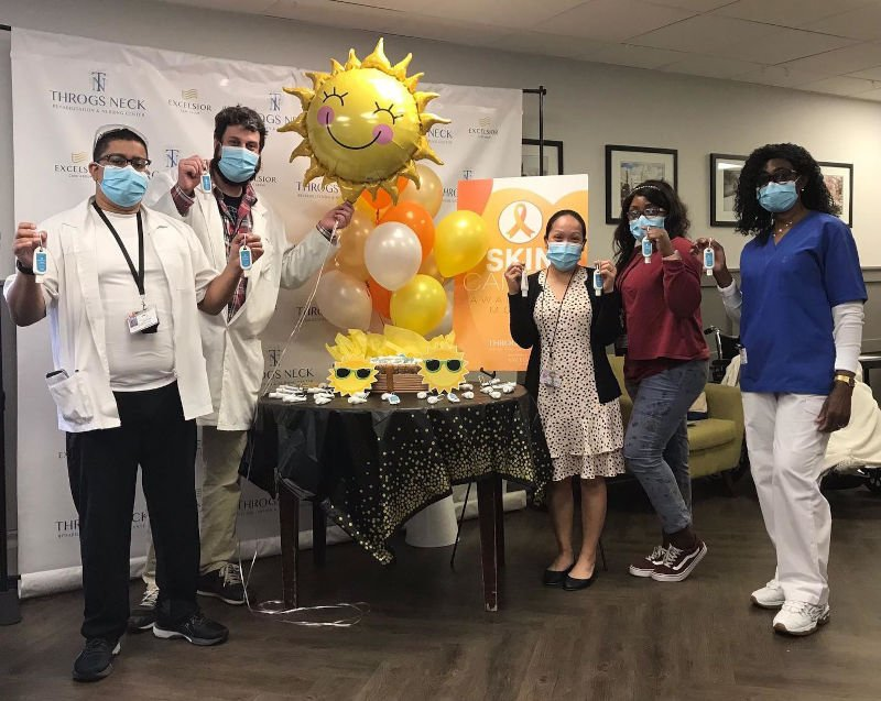 Group of employees stand around table with sunshine balloon